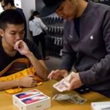 Pengene bliver talt, inden den nye iPhone X bliver udleveret fra Apples butik i Hongkong fredag morgen. Foto: Anthony Wallace, AFP/Scanpix
