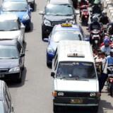 Motorcykler og biler, tæt trafik i Jakarta, Indonesien.