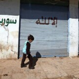 En syrisk skoledreng går forbi en graffiti med teksten »Vi knæler kun for Gud. Befri Syrien.Zohra Bensemra