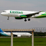 FILE PHOTO: A Citilink Airbus A320 approaches for a landing at Soekarno-Hatta International Airport in Jakarta June 14, 2013. REUTERS/Enny Nuraheni/File Photo