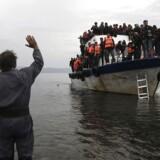 Arkivfoto. En lokal beboer vinker til en overfyldt fiskerbod med flygtninge og migranter, efter de har krydset det Ægæiske hav fra Tyrkiet på vej til Grækenland. EPA/YANNIS KOLESIDIS GREECE OUT