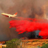 Tirsdag var 20.000 mennesker evakueret og mindst 11 omkommet i de mest katastrofale brande i delstatens historie. De lokale kalder vinden, der bærer flammerne frem, 'Diablo' eller 'Djævlen'. En DC-10 dumper brandhæmmende væske i Orange, Californien.