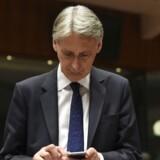 Hammond tjekker sin mobiltelefon ved et EU-møde. / AFP PHOTO / JOHN THYS
