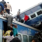 Lokale leder efter overlevende i de ødelagte togvogne. Lørdag kørte et eksprestog af skinnerne nær byen Khatauli in den indiske stat Uttar Pradesh. / AFP PHOTO / -