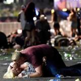 En mand ligger beskyttende oven på en kvinde under masseskyderiet i Las Vegas. Fotografen David Becker (AFP) oplyser til Berlingske, at manden efterfølgende hjalp kvinden op, og at de forlod stedet sammen.
