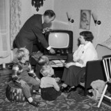 Så er den lille familie klar til at tænde for fjernsynet.; A family is ready to watch televison.;