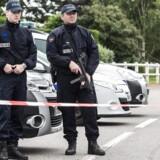 Politibetjente står tirsdag vagt nær huset, hvor en politimand og dennes kæreste blev dræbt mandag aften.EPA/CHRISTOPHE PETIT TESSON