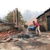 En kvinde hælder vand på et udbrændt område i Vila Nova i Portugal.