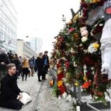 Folk stopper i respekt ved det improviserede mindesmærke over ofrene i Stockholm.