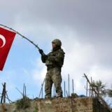 En tyrkisk soldat holder det tyrkiske flag ved byen Afrin i Syrien.