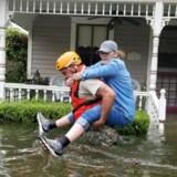En soldat fra nationalgarden i Texas bærer en kvinde gennem vandmasserne i et af de oversvømmede områder af Houston, Texas. Reuters/Handout