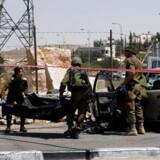 Israelske soldater fjerner liget af en palæstinenser, der ville køre en bil ind i en gruppe mennesker på Vestbredden.