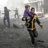 En syrisk mand bærer et barn, der blev såret i regeringens bombning i den oprørerbesatte by Hamouria i det urolige Østghouta, der ligger lidt øst for Damaskus.