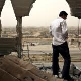 En mand går gennem ruinerne af en bygning i Sadr By, en bydel i Bagdad, der var under angreb i 2008. Foto: Joao Silva/The New York Times