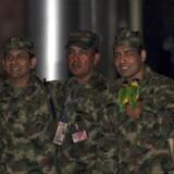 De fire soldater, som tidligere har været i den colombianske oprørsgruppes fangeskab, smiler ved ankomsten i Botogas militærlufthavn.