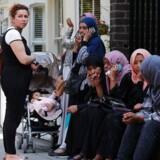 Flere mennesker samles nær Grenfell Tower, en boligblok i det vestlige London, efter en voldsom brand natten til onsdag 14. juni 2017. / AFP PHOTO / Adrian DENNIS