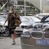 A woman is reflected on the glass wall of a BMW showroom as she walks past it in central Beijing in this August 14, 2012 file photo.