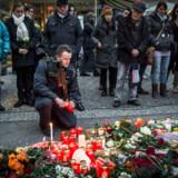 Berlingske fotograf Asger Ladefoged er I Berlin dagen efter terrrorhandlingen mandag aften. En tysk betjent tænder et lys for de omkomne.