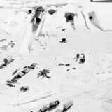 Den amerikanske Grøndlandsbase »Camp Century« havde indtil 1967 en fungerende atomreaktor kørende under indlandsisen. Reaktoren efterlod lavradioaktivt spildevand - og hvis isen smelter, vil det radioaktive vand frigives. Derfor er forskere nu igang med at undersøge det præcise omfang af radioaktiviteten. Her ses militærfotos af basen.