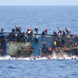Flygtninge og migranter ryger i Middelhavet, da deres skib kæntrer ud for Libyen. Fotoet er taget  fra et af de to italienske  kystvagtskibe, der opholdt sig i nærheden. Foto: Scanpix