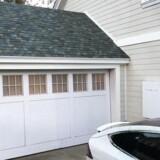 Teslas bud på det moderne hjem med solpaneler indbygget i taget, et særlig batteri til lagring af strøm på husfacaden og en Tesla i en indkørslen.