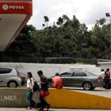 Fodgængere passerer en af PDVSAs benzinstationer i Caracas, Venezuela. Foto: Marco Bello/Reuters