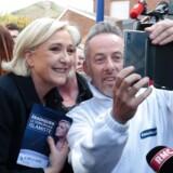 Front Nationals Marine Le Pen var efter søndagens første runde af det franske præsidentvalg i fulde omdrejninger med valgkampen fra mandag morgen. Her poserer hun sammen med en tilhænger i Rouvroy i det nordlige France. / AFP PHOTO / joel SAGET