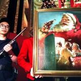 Hele to af klummeskribentens laster er indlejret i dette oprindelige oliemaleri af Julemanden med en cola i hånden, et kunstværk der her udstilles under bevogtning i Hong Kong, AFP PHOTO/Robyn BECK ROBYN BECK / AFP
