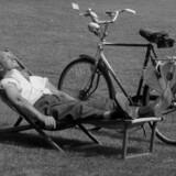 Danmark Dengang 1957. Mand nyder solen i en medbragt liggestol og cyklen parkeret ved siden af.