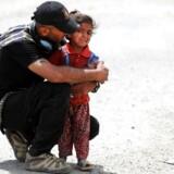 En irakisk soldat hjælper en lille pige i det vestlige Mosul.
