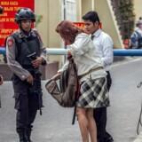 Bevæbnede betjente undersøger en kvindes taske i nærheden af politiets hovedkvarter i byen Medan i det nordlige Sumatra. Indonesiens antiterrorkorps har gennemført razziaer over hele landet i jagten på militante islamister efter flere dødelige angreb de seneste dage. Scanpix/Ivan Damanik