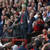 Showmanden Arsene Wenger for Arsenal, når han var bedst. Forvist til tilskuerpladserne på Old Trafford i en kamp mod rivalerne fra Manchester United.