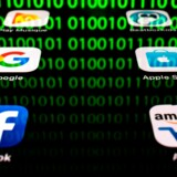 (FILES) In this file illustration picture taken on April 20, 2018 in Paris shows apps for Google, Amazon, Facebook, Apple (GAFA) and the reflexion of a binary code displayed on a tablet screen. The EU's new data protection rules that enter into force later this month are having an impact around the world as firms, including in the United States and China, move to comply. / AFP PHOTO / Lionel BONAVENTURE