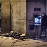 Arkivfoto: Klokken passerer snart 6.30 tidlig søndag morgen d. 18. December. Foran Danske Bank på Vesterbrogade i København ligger en hjemløs og sover, mens en forbipasserende hæver kontakter i automaten ved siden af.. (Foto: Asger Ladefoged/Scanpix 2017)