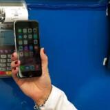 Apple Pay, som er Apples mobilbetalingssystem, virker kun på de nye iPhone 6-telefoner. Man lægger sine kreditkortoplysninger ind og kan så betale ved at føre telefonen hen over de særlige terminaler, som kan aflæse telefonens oplysninger. Arkivfoto: Bryan Thomas, Getty Images/AFP/Scanpix