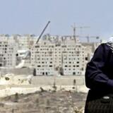 Israels plan om at udvide bosættelsen Har Homa i det sydøstlige Jerusalem kan sætte en stopper for de nystartede fredsforhandlinger mellem Israel og palæstinenserne. Her venter en palæstinensisk kvinde ved en kontrolpost udenfor Har Homa. Arkivfoto: Natalie Behring/Scanpix