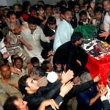 Tilhængere og familie sænker Bebazir Bhuttos kiste i jorden.