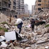 Folk går med deres ejendele igennem den den sønderbombede by Aleppo i Syrien 17. december.