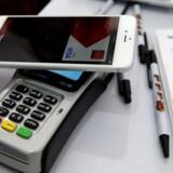 Apple Pay virker kun på de nyeste telefoner og kun, når udstederen af ens kreditkort har en aftale med Apple, og kortlæseren kan modtage signalet fra telefonen. Man holder telefonen op til kortlæseren og godkender så med sit fingeraftryk betalingen. Arkivfoto: Justin Sullivan, Getty Images/AFP/Scanpix