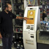 A man demonstrates the use of a Bitcoin ATM at a bookstore in Acharnai in northern Athens, Greece June 30, 2015.