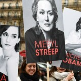 Meryl Streep og Emma Watson er blandt de otte skuespillerinder, som vil tage køns- og raceaktivister med til prisuddelingen Golden Globe. Her ses de på plakater under Womans Day i Paris i marts 2017. AFP PHOTO / GABRIEL BOUYS