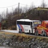Bussen fra Valdresekspressen, hvor en asylansøger mandag dræbte tre, trækkes væk fra gerningsstedet på rigsvej 53 ved Holsbru mellom Årdal og Tyin.