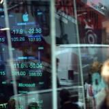 På Wall Street ser en fodgænger bekymret på aktiekurser i et vindue.