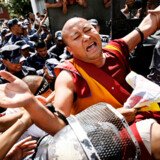 En tibetansk munk bliver anholdt under en protest uden for den kinesiske ambassades visumkontor i Nepals hovedstad, Katmandu. Kina strammer op for visumreglerne op til OL, hvilket går ud over udenlandske virksomheder og studerende.