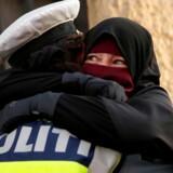 En betjent omfavner en niqab-bærende kvinde ved en demonstration imod tildækningsforbuddet i København 1. august.