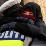 Fotografiet af en kvindelig dansk politibetjent, som omfavner en niqabklædt demonstrant, er gået verden rundt – og har fået Venstres Marcus Knuth til at kritisere politiet.