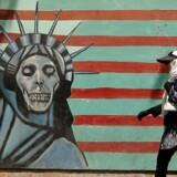 En iransk kvinde går forbi den tidligere amerikanske ambassade i Teheran 7. august 2018. / AFP PHOTO / ATTA KENARE