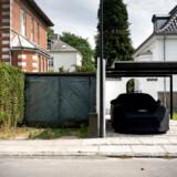 Ingen ved, hvad der gemmer sig i garagen til venstre. I den åbne carport til højre holder en Aston Martin i skræddersyget regntøj og gør sig til. Det er ikke lige meget, hvordan man viser sin rigdom i Hellerup