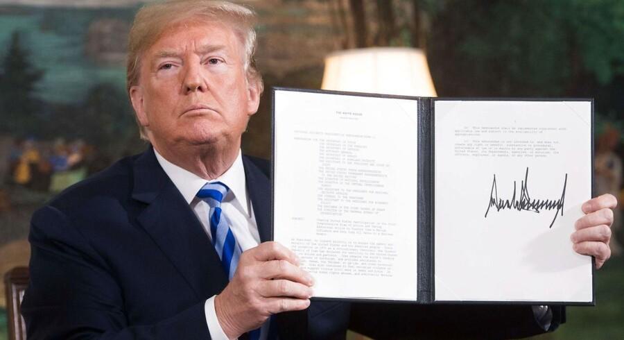 USAs præsident Donald Trump holder et dokument, som viser, at landet genindfører sanktionerne mod Iran. Det sker efter. at Trump har erklæret, at USA trækker sig fra den internationale atomaftale med Iran. / AFP PHOTO / SAUL LOEB