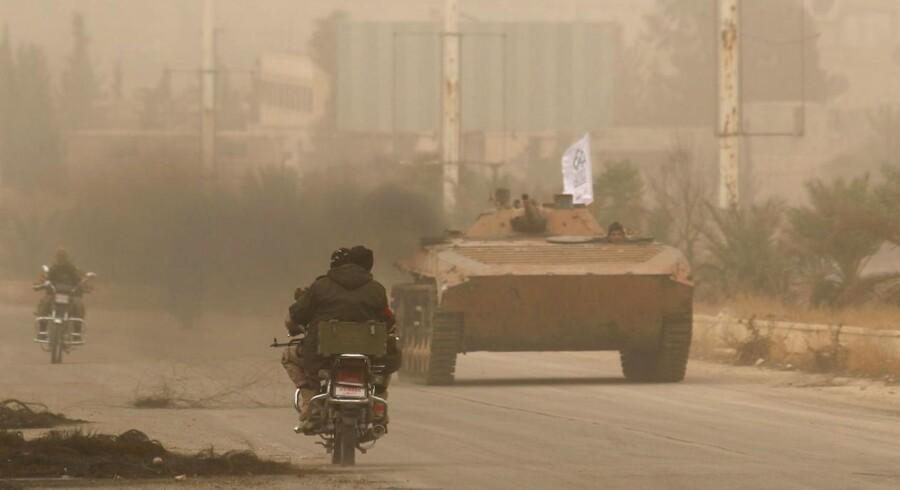 Oprører kører afsted i Dahiyat al-Assad i det vestlige Aleppo i Syrien.